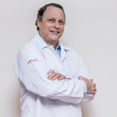 Dr. Philip Wolff, de jaleco e braços cruzados, especialista em inseminação artificial.
