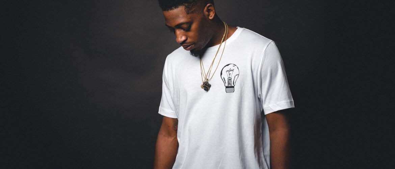 Homem negro de cabeça baicxa, camiseta branca com infertilidade masculina
