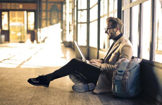 Infertilidade masculina. Homem sentado no chão com notebook sobre o colo.