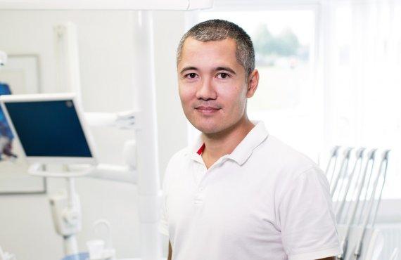 Homem de camiseta branca em consultório médico.