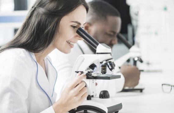 Mulher em laboratório de reprodução humana assistida olhando por microscópio