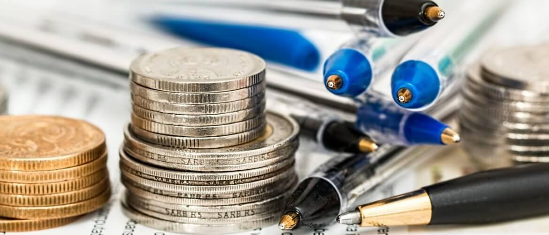 moedas, canetas e papel para calcular quanto custa a FIV