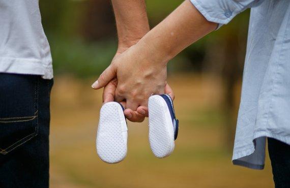 Casais soropositivos de mãos dadas segurando sapatinhos de bebê
